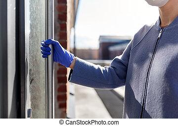 woman in protective glove trying to open door