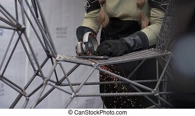 Woman in protective helmet using metall cutting machine in...