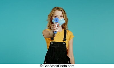 Woman in protective mask directs electronic non-contact thermometer into camera lens and measures temperature. Shows with gesture that everything is fine, temperature is normal Blue studio background