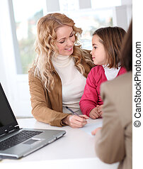 Woman in real-estate agency with kid