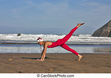 Woman in red and Christmas hat make gymnastic on the beach