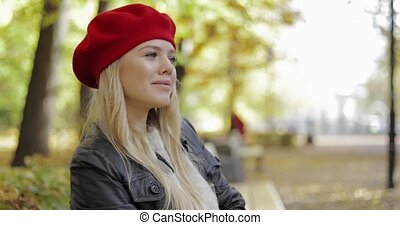 Woman in red beret relaxing on bench - Attractive young...