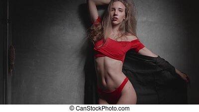 Woman in red bikini over gray wall studio background