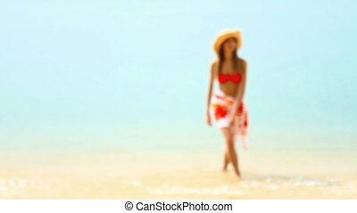 Woman in red bikini walking at tropical beach in sunshine