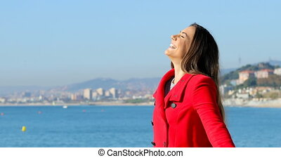 Woman in red breathing fresh air in winter on the beach