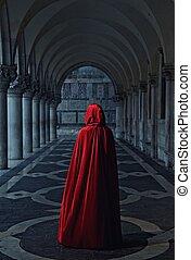 Woman in red cloak walking away