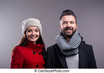 Woman in red coat and hipster man. Studio shot