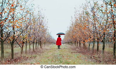 Woman in red coat, hat and umbrella walking alone between...