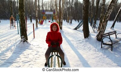 Woman in red coat rocks on winter seesaw