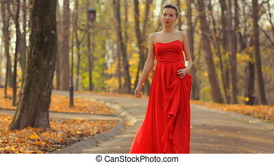 Woman in red dress and beautiful red fashionable shoes walking like a princess in the park.