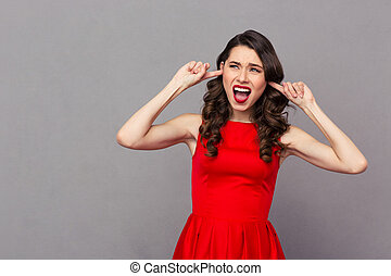 Woman in red dress covering her ears with fingers