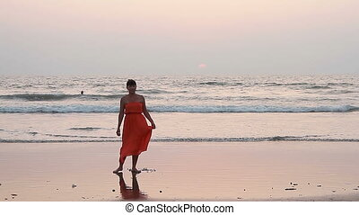 Woman in red dress dancing on the beach.