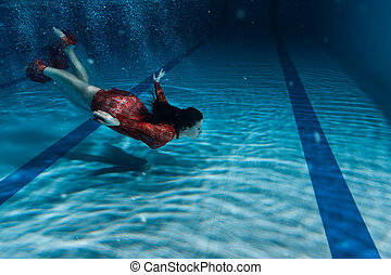 Woman in red dress dives.
