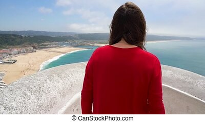 Woman in red dress enjoys a view of the ocean coast near Nazare, Portugal. Slow motion