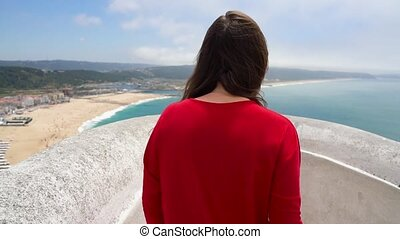 Woman in red dress enjoys a view of the ocean coast near Nazare, Portugal