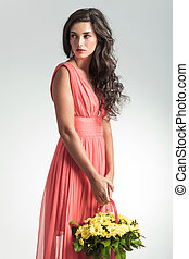 woman in red dress holding flower basket looks to side