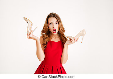 Woman in red dress holding pair of high heels shoes