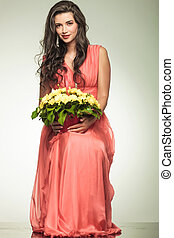 woman in red dress holding yellow flowers basket and sits