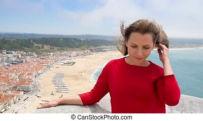 Woman in red dress relaxing on top of a hill above the city of Nazareth, Portugal, slow motion