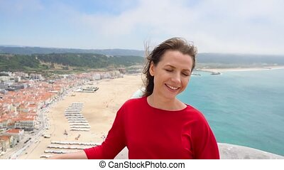 Woman in red dress relaxing on top of a hill above the city of Nazareth, Portugal