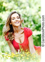 Woman in red dress sitting on grass