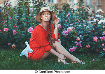 Woman in red dress sitting on the grass.