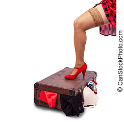 woman in red dress standing her leg on a suitcase