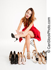Woman in red dress trying on new high heels shoes