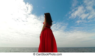 beautiful woman walking down pier in long red dress