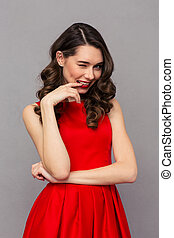 Woman in red dress winking at camera