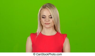 Woman in red dress winks with one eye. Green screen