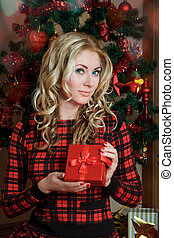 Woman in red dress with gift-box under Christmas tree