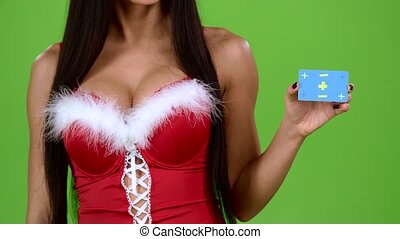 Woman in red erotic underwear shows a card. Green screen. Close up. Slow motion