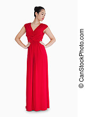 Woman in red evening gown with her hands on her hips