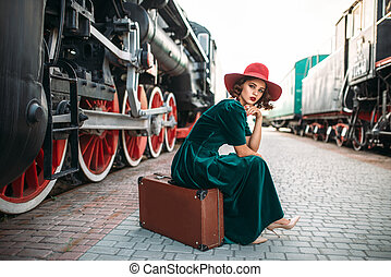 Woman in red hat against vintage steam train - Woman in red...