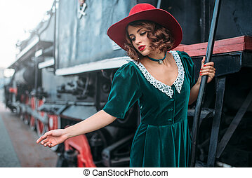 Woman in red hat on vintage steam locomotive. Old train....