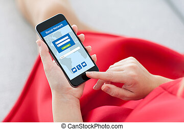 woman in red holding phone with social network on screen -...