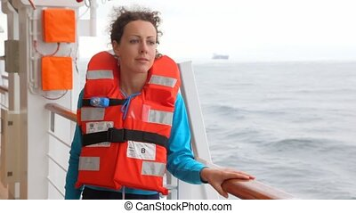 woman in red life jacket looks at waves from ship board