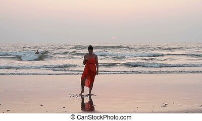 Woman in red sarong dancing on the beach.