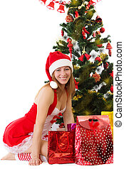 Woman in red sitting under Christmas tree with gifts