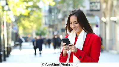 Woman in red texting on phone in winter