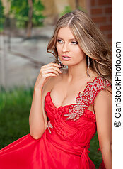 Woman in red. Thoughtful young woman in red dress looking away