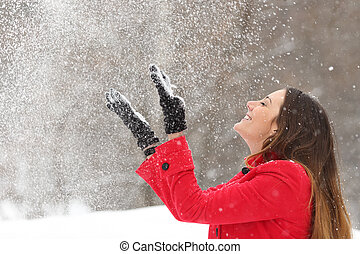 Woman in red throwing snow in the air in winter - Woman ...