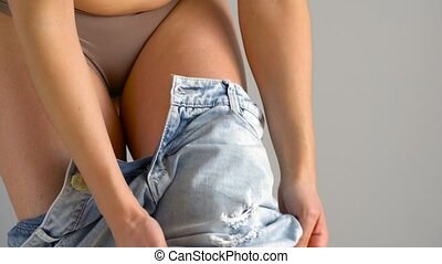 Woman in red underwear pulls on blue jeans - Woman in red...