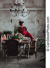 Woman in red vintage dress sits on the table served for christmas diner. Loft interior with clear concrete wall