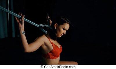 Female in red bra demonstrate bdsm tools sitting on black sofa backstage