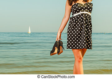 Woman in retro dress holding shoes near sea - Relaxation...