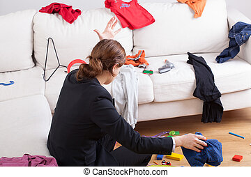 Woman in room of messy clothes
