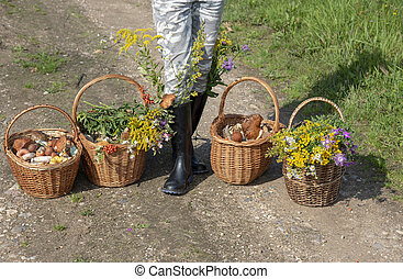 Woman in rubber boots with baskets of mushrooms and flowers