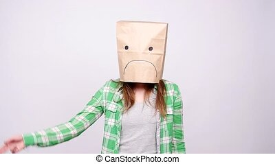 Woman in sad ecological paper bag on head - young woman in...